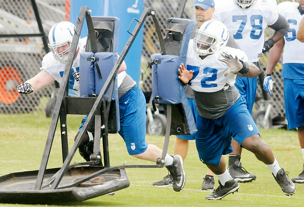 Don Knight   The Herald Bulletin<br /> From left, Jack Mewhort and Jonotthan Harrison hit a sled during Colts practice on Saturday.