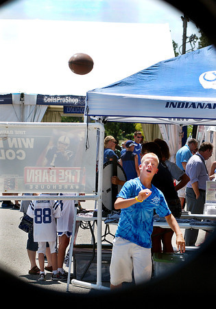 Noah Bozell, 12, of Pendleton, throws the football toward the tire target at the Tire Barn booth in Colts City to try to win a prize.