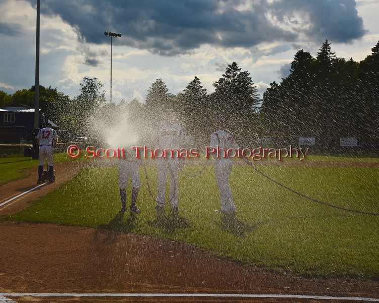 Cortland Crush players watering down the infield before playing the Syracuse Junior Chiefs on Greg's Field at Beaudry Park in Cortland, New York on Friday June 5, 2015.