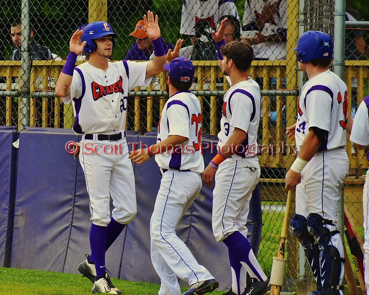 Cortland Crush Chris Mattison (20) high fives his teammates after scoring a run against the Syracuse Junior Chiefs on Greg's Field at Beaudry Park in Cortland, New York on Saturday June 20, 2015. Cortland won 4-1.
