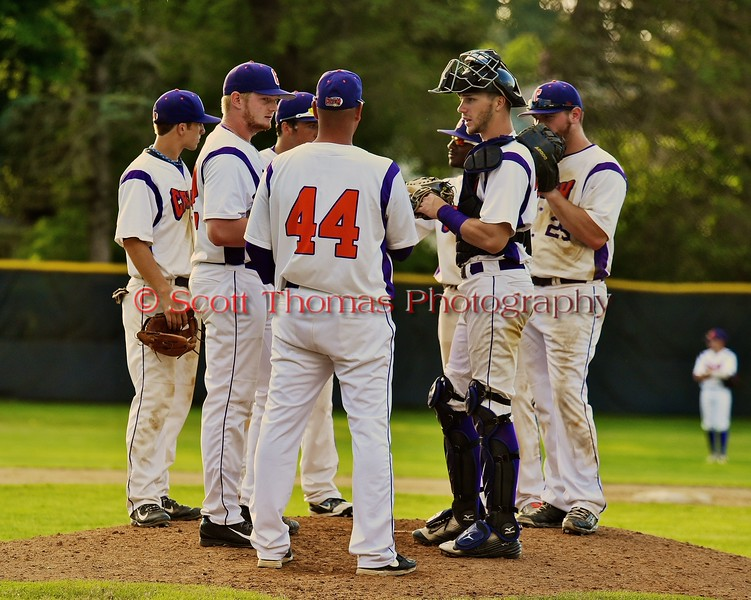 Cortland Crush Head Coach Daniel Payne (44) meets with the team on the mound during the game against the Oneonta Outlaws on Greg's Field at Beaudry Park in Cortland, New York on Tuesday, June 23, 2015. Oneonta won 7-5.