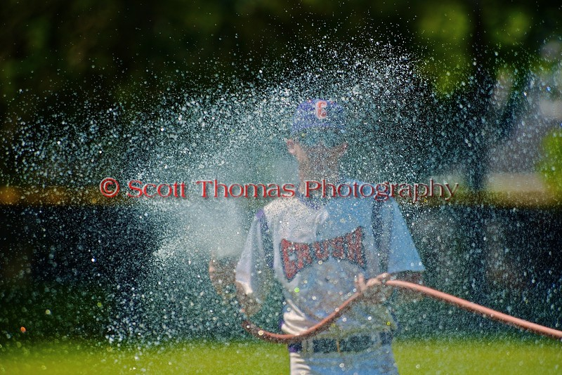 Cortland Crush Assistant Coach Myron Jellison (4) wets down the in-field before the game against the Sherrill Silversmiths on Greg's Field at Beaudry Park in Cortland, New York on Saturday, July 11, 2015.