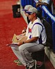 Cortland Crush Head Coach Daniel Payne (44) watching the game against the Syracuse Salt Cats from the dugout in Syracuse, New York on Saturday, July 18, 2015. Cortland won 5-2.