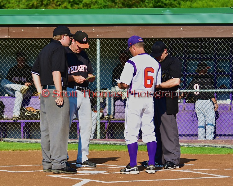 Cortland Crush Manager Bill McConnell goes over pre-game instructions with umpires and the Oneonta Outlaws manager before a NYCBL Playoff game on Greg's Field at Beaudry Park in Cortland, New York on Monday, July 27, 2015.