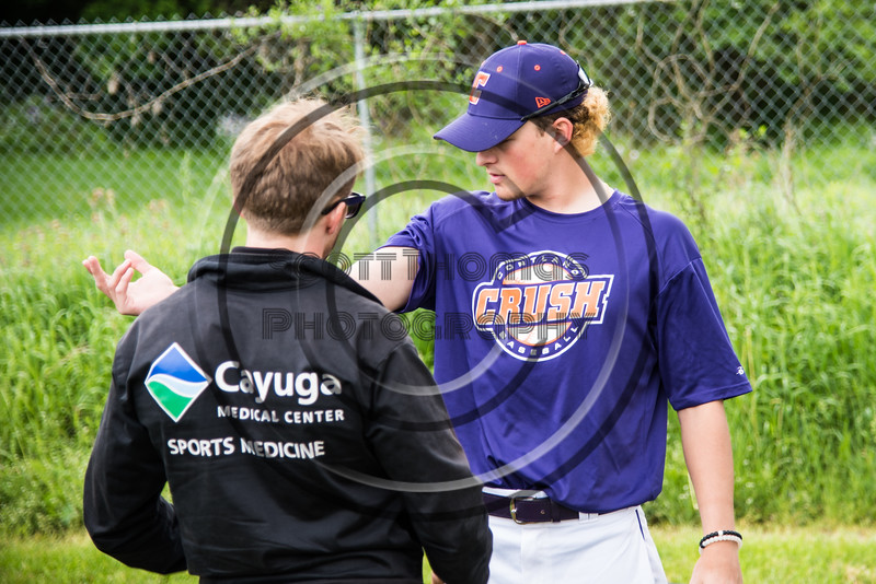 Cortland Crush Athletic Trainer Anthony Spinelli attends to a player on Greg's Field at Beaudry Park in Cortland, New York on Sunday, June 3, 2018.