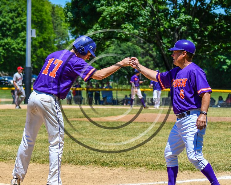 Cortland Crush Head Coach Bill McConnell (6) gives knuckles to Jimmy Tatum (17) after reaching 3rd Base against the Syracuse Salt Cats on Greg's Field at Beaudry Park in Cortland, New York on Saturday, June 16, 2018. Cortland won 10-0.