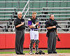 Cortland Crush Catcher Justin Valentino (15) standing with the Umpires during the National Anthem before playing the Rome Generals on Wallace Field in Cortland, New York on Sunday, June 23, 2018.