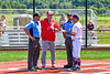 Cortland Crush Head Coach Bill McConnell (6) goes over rosters before with the Umpires and Syracuse Salt Cats Manager in New York Collegiate Baseball League action at Gutchess Lumber Sports Complex in Cortland, New York on Sunday, June 23, 2019.