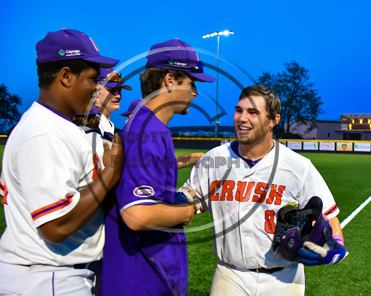 Cortland Crush players congratulating Sean O'Malley (8) for his Walk Off Single to defeat the Syracuse Salt Cats in a New York Collegiate Baseball League playoff game at Gutchess Lumber Sports Complex in Cortland, New York on Thursday, July 24, 2019. Cortland won 1-0 in extra innings.