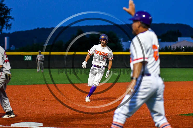 Cortland Crush Nicholas Pastore (1) is held at Thrid Base by Head Coach Bill McConnell (6) against the Syracuse Salt Cats in New York Collegiate Baseball League playoff action at Gutchess Lumber Sports Complex in Cortland, New York on Thursday, July 24, 2019. Cortland won 1-0 in extra innings.