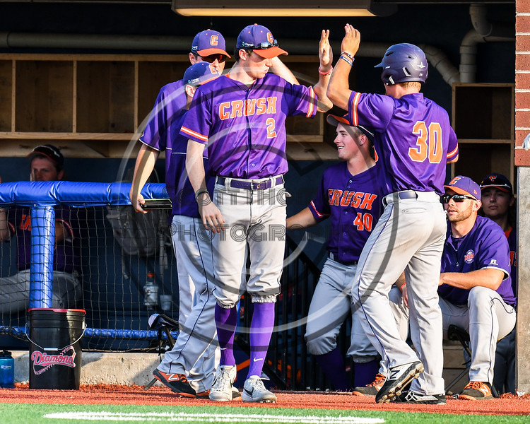 Cortland Crush Jack Lynch (2) congratulates Stephen Bennett (30) for scoring a run against the Syracuse Salt Cats in New York Collegiate Baseball League playoff action at OCC Turf Field in Syracuse, New York on Thursday, July 25, 2019. Cortland won 3-1.