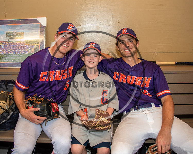 Cortland Crush players Zach Marriott (5) and Rob Ciulla (13) with a new friend in the dugout at Gutchess Lumber Sports Complex in Cortland, New York on Friday, June 18, 2021.