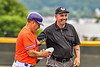 Umpire hands Cortland Crush Manager Bill McConnell some runner equipment during a New York Collegiate Baseball League game at Gutchess Lumber Sports Complex in Cortland, New York on Saturday, June 19, 2021.