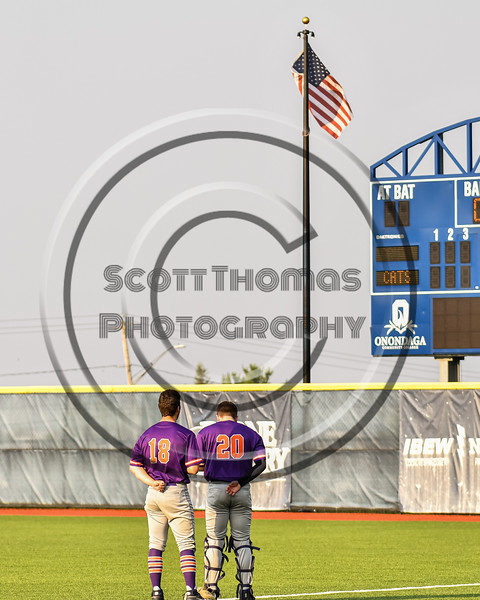 """Cortland Crush players Brandon """"Buzz"""" Shirley (18) and Matthew Ward (20) stand for the National Anthem before playing the Syracuse Salt Cats in a New York Collegiate Baseball League game at OCC Turf Field in Syracuse, New York on Tuesday, July 6, 2021."""