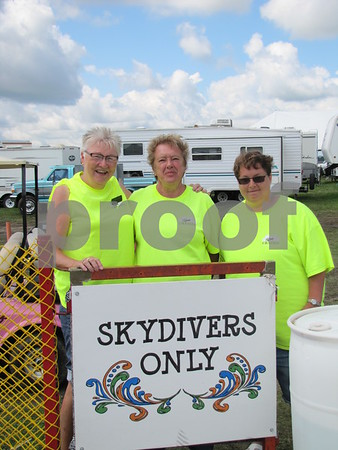 "Volunteers from ""Plane Crazies"" Carol Heatherington, Sue Witt, and Judy Witt guard the gate to the skydivers area."