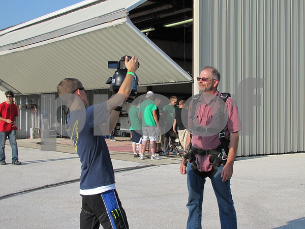 A member of the skydiving club interviews Mike Wiley before his tandem jump.  Wiley was taking the jump to celebrate his 50th birthday.