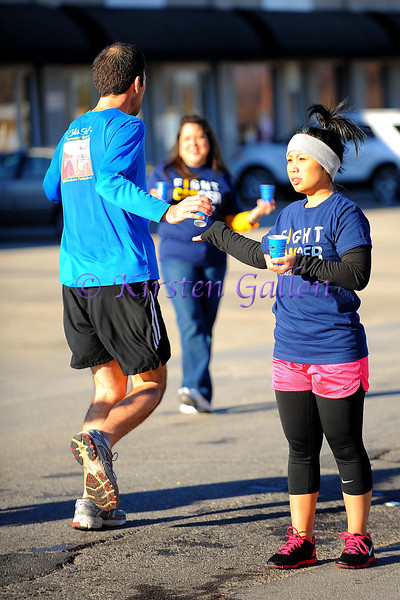 Holly Nguyen helps to hand out water to the runners.