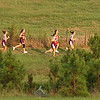 Runners can just be seen over the pines along the course at Daniel Boone High School during the TC Twilight Two CC meet. Photo by Ned Jilton II