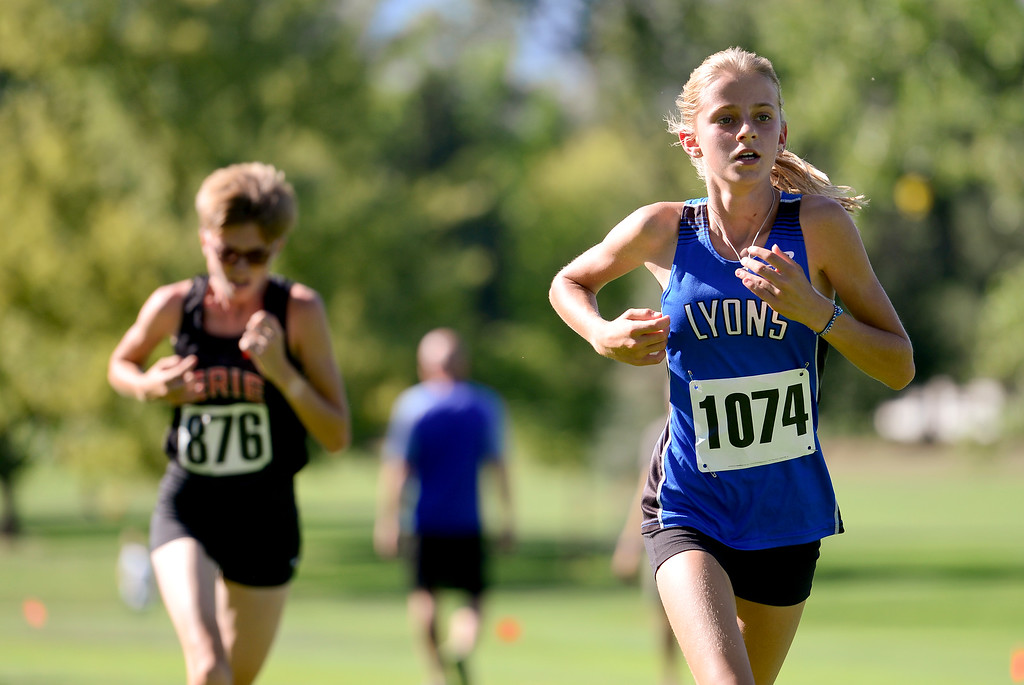 . LONGMONT, CO - SEPTEMBER 12: Lyons High School\'s Quinn Gregg, right, and Erie High Shool\'s Emily Condon, left, battle for position on the course in the RE1J District Meet at Sunset Golf Course in Longmont on Sept. 12, 2018. Gregg finished first in the cross country meet with a time of 21:13.6. (Photo by Matthew Jonas/Staff Photographer)