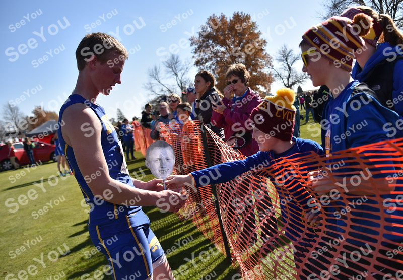 -Messenger photo by Britt Kudla<br /> Humboldt Wade Carson (7 years old) hands his brother Calvin Carson (left) a souvenir after competing during Boys Class 3A State XC meet on Saturday at Lakeside Golf Course