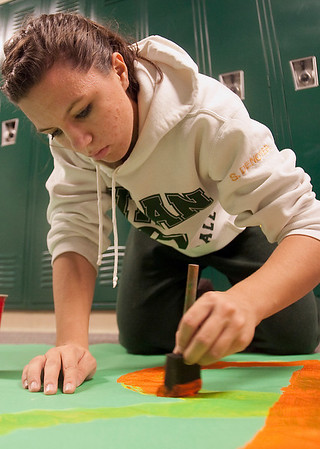 Record-Eagle/Douglas Tesner<br /> Sydney Denoyer, a sophomore and a member of the Traverse City West student senate, prepares banners for the annual rivalry football game between West and Traverse City Central.