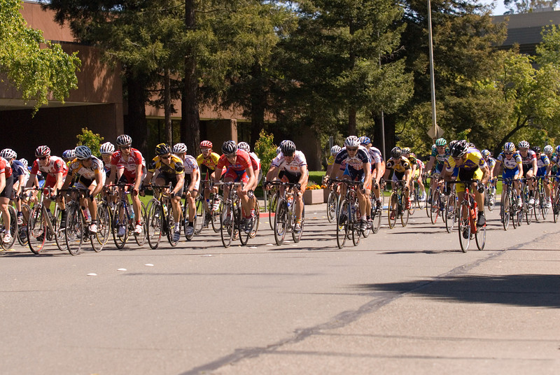 John Simmons (Garden City Cyclists / Shaws' Lightweight cycles), far right, attacks with 2 laps to go.  The peloton on the left all watch him light up the race before responding.