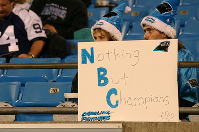 Front-Row Fans behind the Cowboys bench appear with one of the many signs designed to attract television cameras.