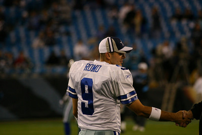 Dallas Cowboys Quarterback Tony Romo shakes hands with a Cowboy coach as he prepares for his first NFL start.