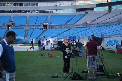 Local media prepare. With the setting sun, the stadium lights made the field and the seats almost glow. Hard-hitting music pumped as they equalized the sound system. Not much conversation. People simply arranging equipment...