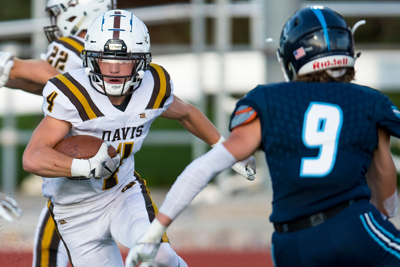 David Spjut (4) of Davis High School cuts around the Layton defender, during the prep football game. In Layton on Friday September 13, 2019.
