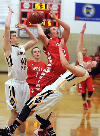 Pat Christman<br /> Mankato West's Ryan Schlichte Collies with Mankato East's Nic Seiler on his way to the basket during the first half Saturday.