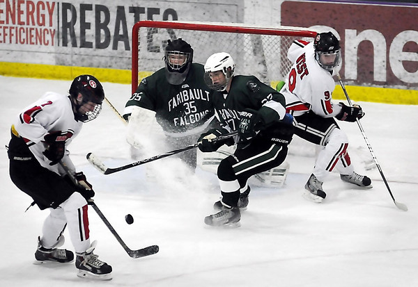 John Cross<br /> Mankato West's Derek Frentz tries to get the puck past Faribault goalie Chase Batchelder and defenseman Koy Payne to teammate Galt Goettl during first period action.