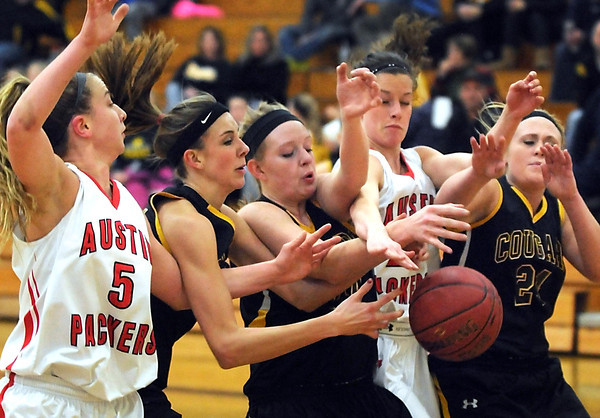 Pat Christman<br /> Mankato East's Taylor Karge (second from left), Claire Ziegler (center) and Paige Lingbeck (right) tangle with Austin's Sayley Vese (5) and Meredity Fritz (24) as they reach for a rebound during the first half Thursday at the East gym.