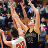 Mankato East's Allison Taylor reaches over a pair of Marshall defenders for a rebound during the first half Saturday at the East gym.