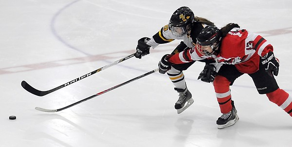 Pat Christman<br /> Mankato East's Amanda Broman has the puck tipped away from her by Mound Westonka's Liz Schepers during the third period Thursday at All Seasons Arena.