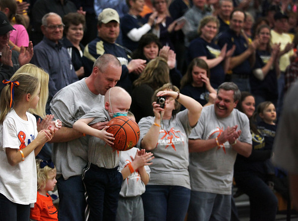 Rick Johnson kisses his son Luke at Teutopolis High School before the game between the Wooden Shoes and the Flaming Hearts. Both teams signed a ball, which they presented Luke, a St. Anthony kindergartener battling leukemia.