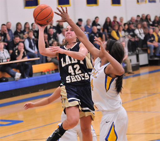 T-Town's Madeline Hartke drives past CHBC's Micah Jones for two of her game-high 20 points in the Lady Shoes' 52-44 victory