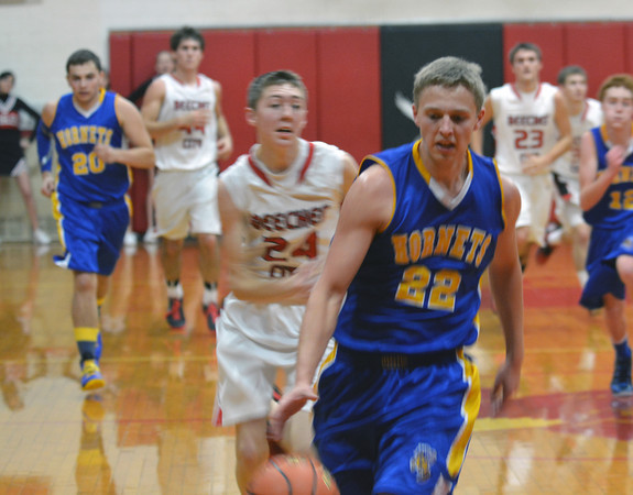 Cowden-Herrick's Colton Burrus takes off on a fast break while Beecher City's Austin Rexroad gives chase behind him.