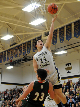 Teutopolis' Bobby Wenthe goes for a layup and draws contact from Salem's Nick Conklin (23) during the Wooden Shoes' Homecoming win.