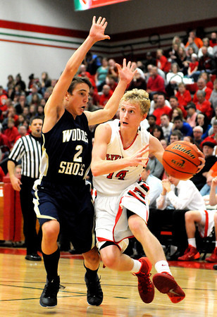 Effingham's Kennan Mahaffey drives toward the basket with Teutopolis' Michael Drees draped all over him during the Effingham-Teutopolis Christmas Classic championship game.