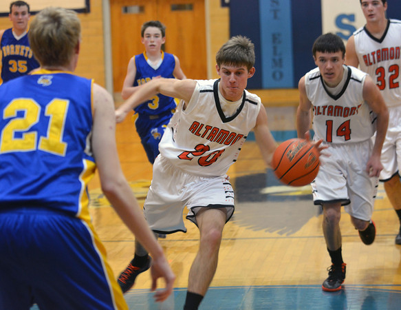 Altamont's Garrett Ziegler triggers a fast break and dribbles into the paint while Cowden-Herrick's Carson Lorton (21) awaits defensively at the St. Elmo Holiday Tournament.