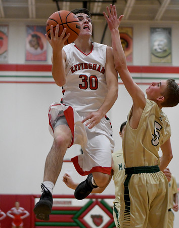 Effingham's Brent Beals goes for a layup against Mattoon's Jacob Ghere Friday evening at Effingham High School.