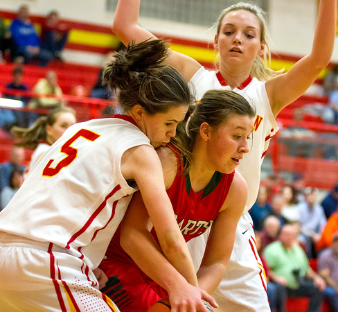Effingham's Carsyn Fearday, center, fends off Charleston's Aislinn Parish, left, and Paige Swango, right, during the Apollo Conference opener, which the Hearts won 57-46.