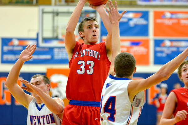 St. Anthony's Drew Gibson shoots a jumper between Newton's Mitch Jansen (left) and Zach Jansen (right). Gibson had 24 in the Bulldogs' win at Newton.