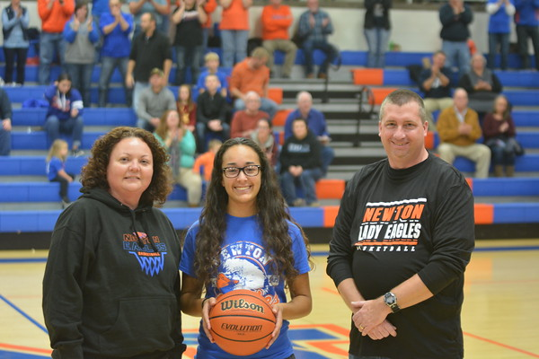 Newton's Ariel Richards (center) is presented the game ball from the Lady Eagles' game against Paris, where Richards scored her 1,000th career point. With her is Newton assistant coach Amy Harris and Newton head coach Brad Harris before a boys basketball game.