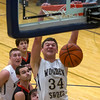 Teutopolis' Mitch Hardiek hangs on the rim after completing an alley-oop dunk while players look on in the background.