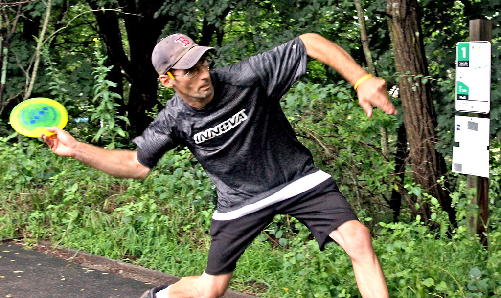 . Paul Adorno,36 of Connecticut, lets a disc fly during a Disc Golf tournament in Devens. SUN/David H. Brow