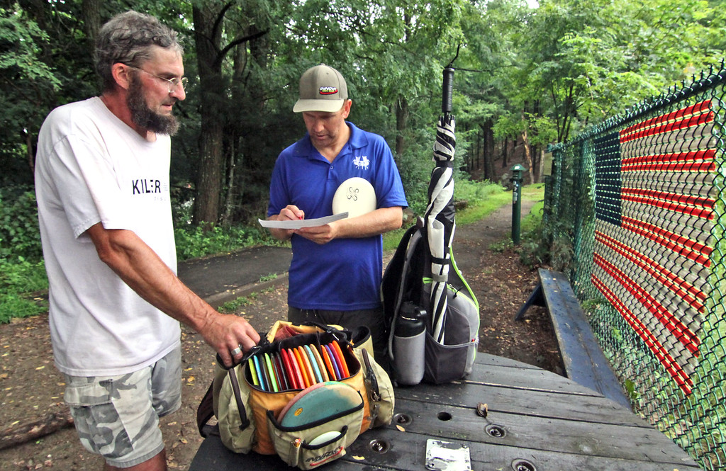 . Disc Golf players, John Rodenhizer of NH and Isaac Bromberg of EastHampton,MA, check their scores after a round. SUN/David H. Brow
