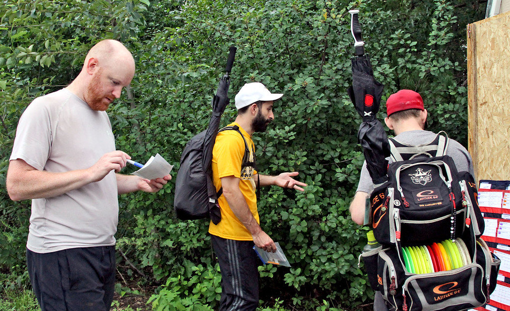 . Disc Golf tournament director, Bill Bertera,on left, checks the scores of a group as they finish the 2nd round. SUN/David H. Brow
