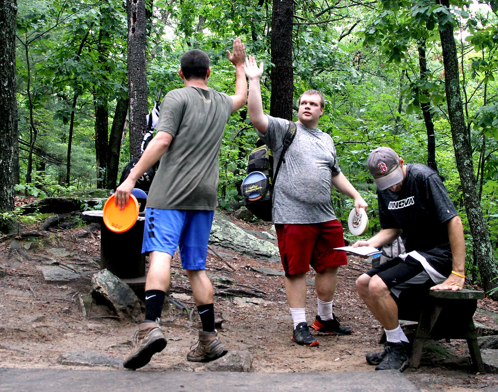 . Team-mates high-five after finishing a good round of Disc Golf, L-R, Tyler Blanchet, Chris Spear and Paul Adorno, all from Connecticut. SUN/David H. Brow